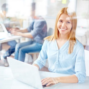 Young secretary looking at camera while typing in office