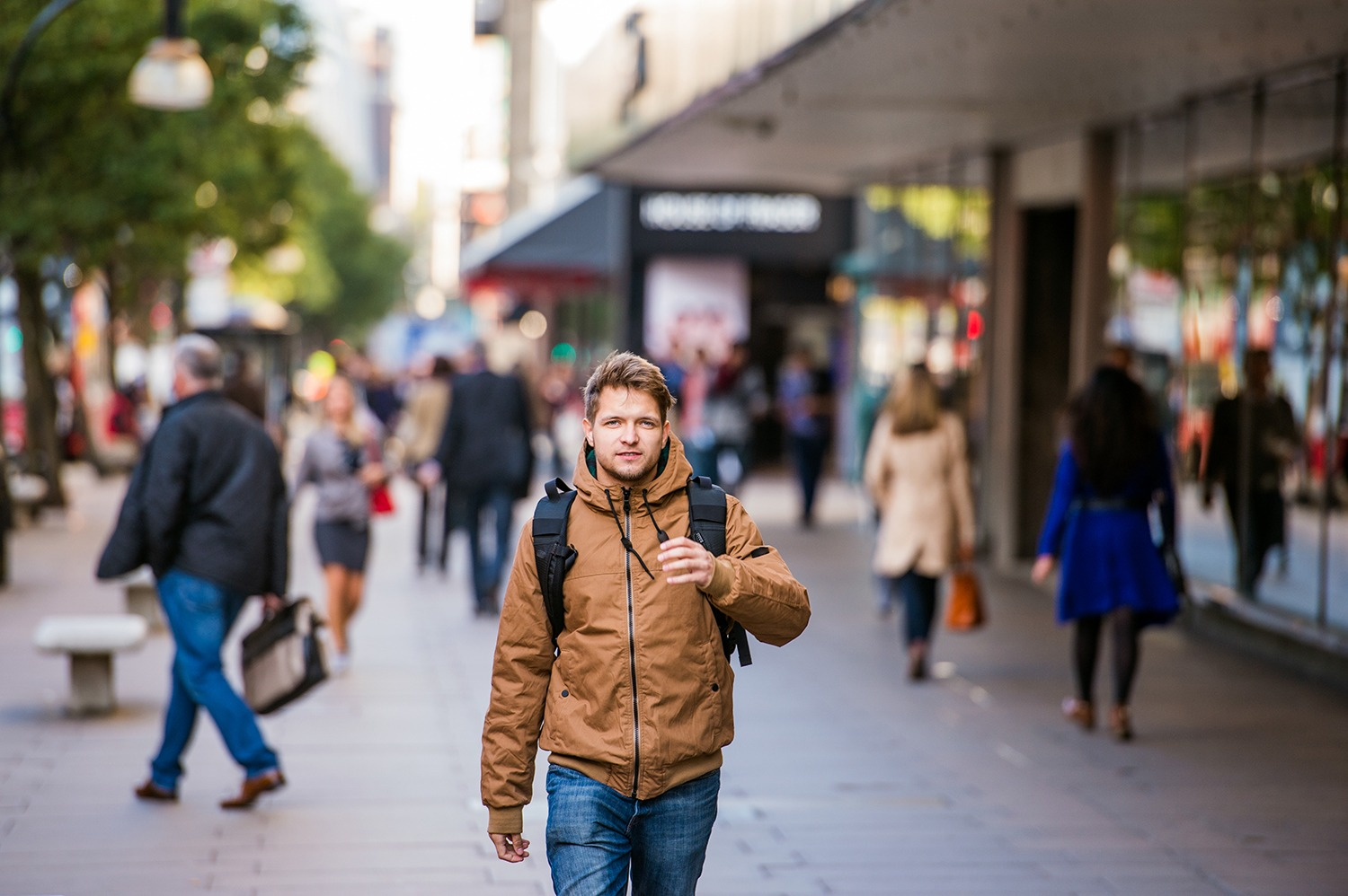 Young hipster man in brown winter jacket walking in the streets of London